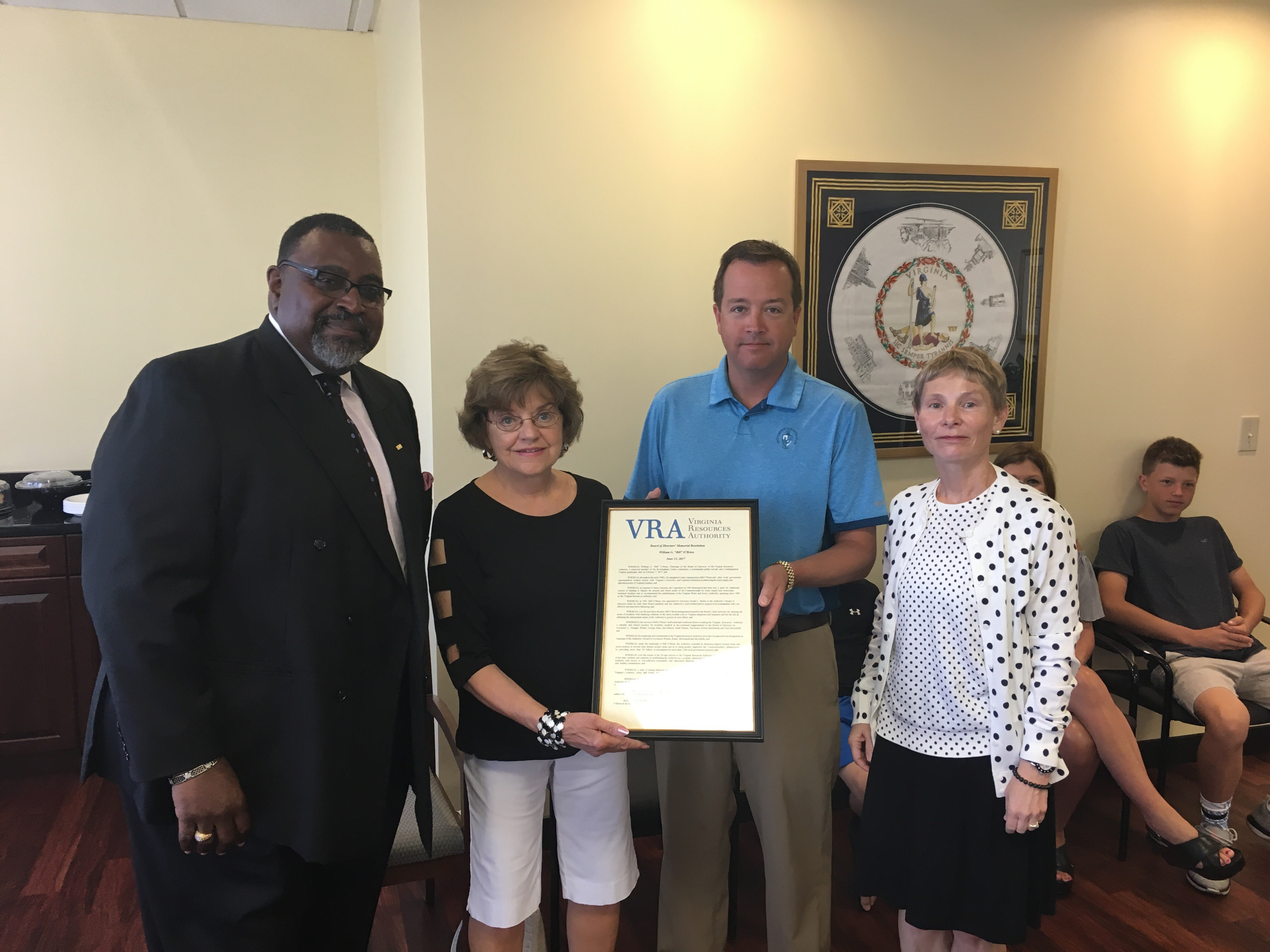 VRA Board Vice Chairman Thomas Hasty and VRA Executive Director Stephanie Hamlett present Mr. O'Brien's wife Jeanne and son Kyle with the VRA Resolution honoring his service to the Commonwealth.